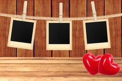 La photo carde accrocher sur la corde sur des pinces à linge et deux coeurs rouges Photos stock