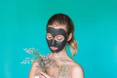 La photo de beauté d'une femme avec un masque noir sur son visage tient les fleurs sauvages sèches à l'arrière-plan contre un mur photo libre de droits