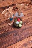 La photo de ci-dessus des lapins de Pâques en bois s'approchent du panier d'oeufs Images libres de droits