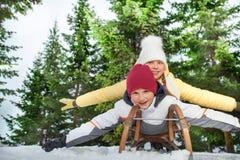 La photo de deux amis sledging ventre-battent à plat de couture au bois Images libres de droits