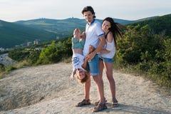 La photo de famille dans les montagnes avec l'enfant portant le fils léger d'habillement accrochant dans le ` s de papa remet à l Photo stock