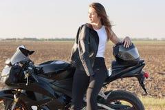 La photo de la femelle caucasienne réfléchie aime monter la motocyclette, pose près de son vélo rapide, a la veste en cuir sur l' image libre de droits
