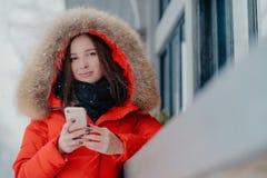 La photo de la femme attirante tient l'instrument moderne moderne, utilise la veste rouge avec hoody, boîte d'email de contrôles, photos stock