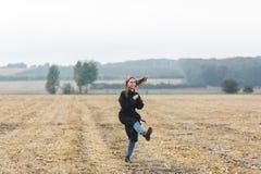 La photo de la femme gaie heureuse ayant l'amusement sur le champ de blé, belle brune avec augmenté remet apprécier la liberté Photographie stock libre de droits