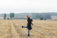La photo de la femme gaie heureuse ayant l'amusement sur le champ de blé, belle brune avec augmenté remet apprécier la liberté Photos stock