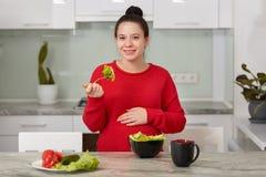 La photo de la future mère mange de la nourriture saine, maison a fait la salade de légume frais à partir du poivre, de la laitue photo stock