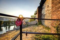 La photo de HDR du soleil de coucher du soleil brillant par l'amour ferme à clef accrocher sur un rail métallique Photos libres de droits