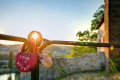 La photo de HDR du soleil de coucher du soleil brillant par l'amour ferme à clef accrocher sur un rail métallique Photographie stock