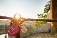La photo de HDR du soleil de coucher du soleil brillant par l'amour ferme à clef accrocher sur un rail métallique Image stock
