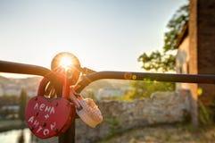 La photo de HDR du soleil de coucher du soleil brillant par l'amour ferme à clef accrocher sur un rail métallique Photographie stock libre de droits