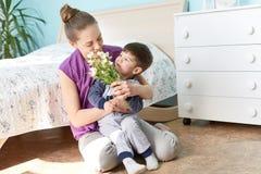 La photo de la jeune femelle agréable à regarder tient son petit fils mignon sur des mains, jeu ensemble dans la chambre à couche photographie stock libre de droits