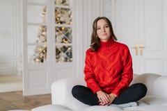 La photo de la jeune femme agréable à regarder habillée dans le chandail rouge, pantalons, repose les jambes croisées sur le diva photographie stock libre de droits