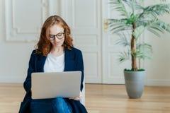 La photo de la jeune femme belle de gingembre dans les lunettes observe la vidéo d'instruction en ligne, des poses dans le divan  photos stock