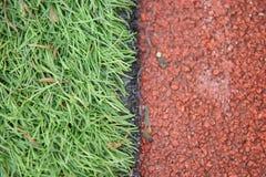 La photo de l'athlétisme artificiel de plan rapproché avec l'herbe verte a combiné avec l'herbe artificielle image stock