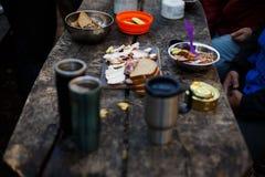 La photo de la table en bois de petit déjeuner du ` s de randonneur avec du pain, le lard, les boîtes, d'autres repas et les tass Photographie stock