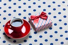 La photo de la tasse rouge du café et du cadeau mignon sur le blanc a pointillé le CCB Photo stock