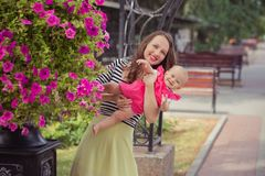 La photo de la mère de brune de jeune dame dans la couleur douce de chemise et d'ivoire de zèbre bordent jouer heureux avec la fi Photo stock