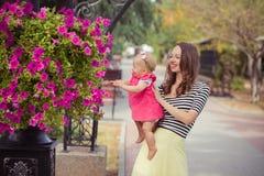 La photo de la mère de brune de jeune dame dans la couleur douce de chemise et d'ivoire de zèbre bordent jouer heureux avec la fi Photographie stock