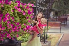La photo de la mère de brune de jeune dame dans la couleur douce de chemise et d'ivoire de zèbre bordent jouer heureux avec la fi Images libres de droits