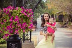 La photo de la mère de brune de jeune dame dans la couleur douce de chemise et d'ivoire de zèbre bordent jouer heureux avec la fi Photos stock
