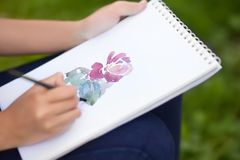 La photo de plan rapproché de la peinture de mains de femme s'est levée avec l'aquarelle Image stock