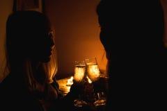 La photo de silhouette de deux filles font tinter des verres avec le champagne Lumière de bougie Photographie stock