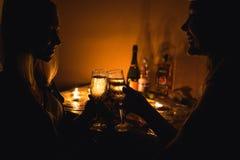 La photo de silhouette de deux filles font tinter des verres avec le champagne Lumière de bougie Image stock