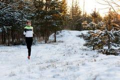 La photo de la sportive gaie dans des espadrilles le matin fonctionnent dans la forêt d'hiver Photographie stock