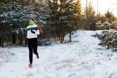 La photo de la sportive gaie dans des espadrilles le matin fonctionnent dans la forêt d'hiver Photographie stock libre de droits