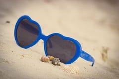 La photo de vintage, les lunettes de soleil bleues a formé le coeur avec des coquilles sur le sable Photo stock