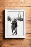 La photo des aînés dans le cadre de tableau s'est étendue sur le fond en bois Photographie stock