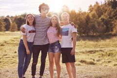 La photo des amis intimes se tiennent extérieure, ont le pique-nique ensemble, l'embrassent et sourient heureusement à l'appareil Photos libres de droits