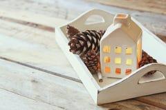 La photo des cônes décoratifs de maison et de pin à côté de la guirlande d'or s'allume sur le fond en bois Copiez l'espace Rétro  Photo stock