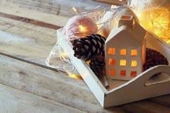 La photo des cônes décoratifs de maison et de pin à côté de la guirlande d'or s'allume sur le fond en bois Copiez l'espace Rétro  Images stock