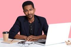 La photo du mâle beau d'afro-américain prenant le frein du travail avec l'ordinateur portable, regards axuasted à la caméra, a dé photos libres de droits