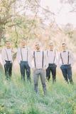 La photo du marié moderne-habillé et ses meilleurs hommes pendant le ressort vert mettent en place Image stock