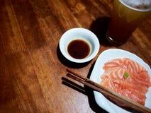 La photo du sashimi, de la sauce à shoyu et de la bière saumonés sur le woode photos stock