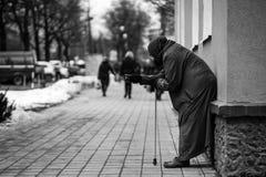 La photo du vieux mendiant féminin sans abri affamé prient pour l'aumône et sur la rue photos libres de droits