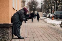La photo du vieux mendiant féminin sans abri affamé prient pour l'aumône et sur la rue images libres de droits
