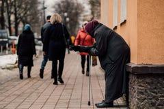 La photo du vieux mendiant féminin sans abri affamé prient pour l'aumône et sur la rue image libre de droits