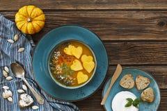 La photo en gros plan de deux plats avec la soupe faite maison fraîche à crème de potiron avec des graines et le coeur forment de Photos libres de droits