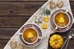 La photo en gros plan de deux plats avec la soupe faite maison fraîche à crème de potiron avec des graines et le coeur forment de Photo libre de droits