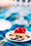La photo en gros plan des sucreries délicieuses de gâteau et de chocolade de fraise d'éponge au fond brouillé du bleu Photographie stock libre de droits
