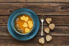 La photo en gros plan du plat avec la soupe faite maison fraîche à crème de potiron avec des graines et le coeur forment des pain Photo stock