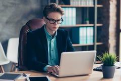 La photo haute étroite de l'entrepreneur bel concentré focalisé de type dans l'eyewear de lunettes d'usage de noir de smoking de  photographie stock