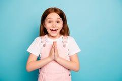 La photo haute étroite des paumes mignonnes étonnées de mains d'enfant parlent en faveur ensemble pour s'attendre au fond bleu d' image stock