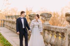 La photo horizontale des mains se tenantes mariées justes et de la marche près de la barrière antique Photo stock