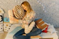 La photo horizontale du jeune adolescent tenant des oreillers avec des lettres d'amour tout en se reposant sur le sofa Images stock