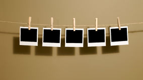La photo instantanée de style polaroïd imprime accrocher sur une corde ou une ligne de lavage, ombres foncées photographie stock