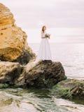 La photo intégrale de la position sur la jeune mariée de falaise au fond de la mer Photos libres de droits